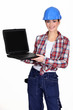 Female manual worker showing off laptop