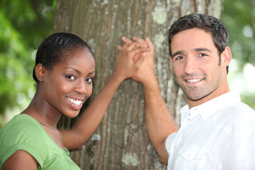 Affectionate couple stood by tree
