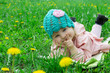 Baby girl lying among field of dandelions
