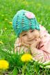 Baby girl lying among field of dandelions