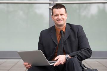geschäftsmann arbeitet draussen am laptop