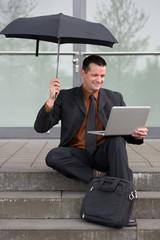 geschäftsmann sitzt mit regenschirm und laptop auf der treppe