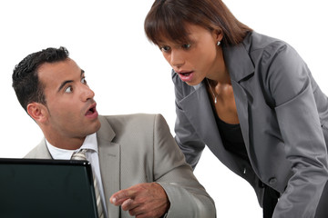 Office workers shocked in front of a computer