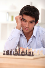 Young man contemplating his next chess move