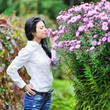 Beautiful youg woman smelling flowers in a garden