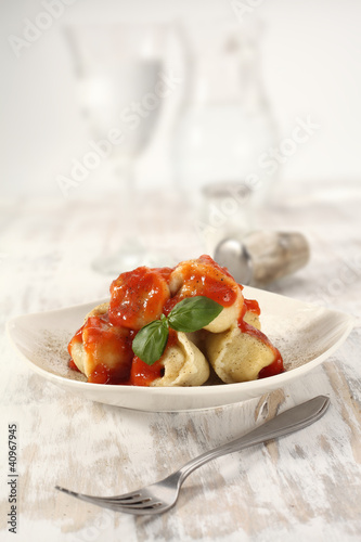 plate on wooden table of ravioli