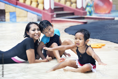 Happy Asian family posing at swimming pool