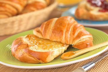 Croissant mit Butter und Orangenmarmelade