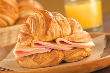 Croissant mit Schinken und Käse auf Rustikalem Holzteller