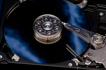 The disassembled hard disk of the computer on a dark blue backgr