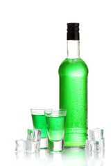 bottle and glasses of absinthe with ice isolated on white