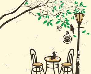 Open-air cafe under a tree with a lantern