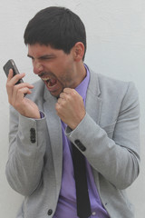 An angry businessman is shouting at his mobile phone
