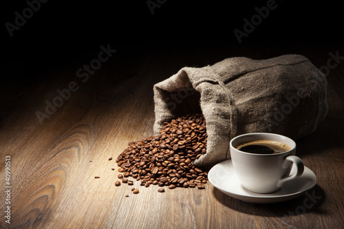Coffee cup with burlap sack of roasted beans on rustic table
