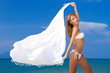 Attractive woman in white bikini holding scarf