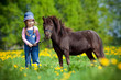 Child and small horse in the field at spring.
