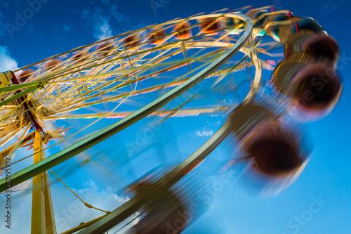 Blurry ferris wheel in motion on blue sky background
