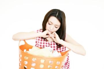 洗濯物を持った不安な表情の女性