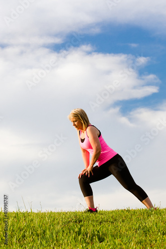 Middle-aged woman in her 40s stretching for exercise outdoors