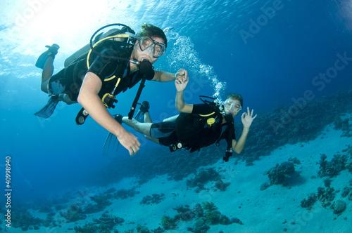 Leinwanddruck Bild man and woman scuba dive togeather