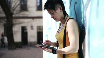 Punk girl with tablet computer standing by the wall