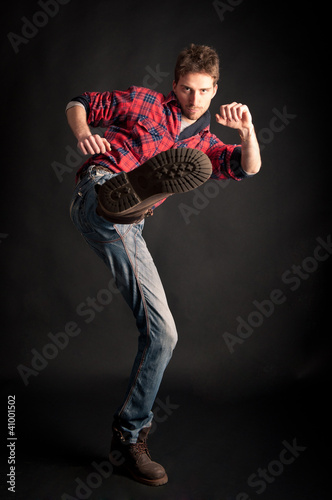 Young man kick against black background.