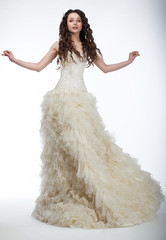 Happy beautiful woman with curly hair in luxurious wedding dress