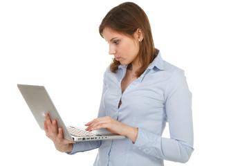 junge frau schaut konzentriert auf ihr laptop