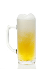 Glass of beer with froth on a white backround