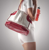 Athletic woman with a sports bag and sports drink