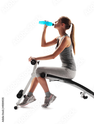 Thirsty young woman drinking after fitness workout.