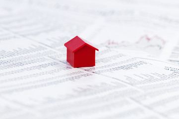 Page of stock market prices with red model house