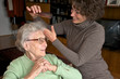 Ältere Dame mit Betreuerin beim Frisieren