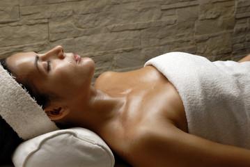 Joven mujer relajándose en un spa.