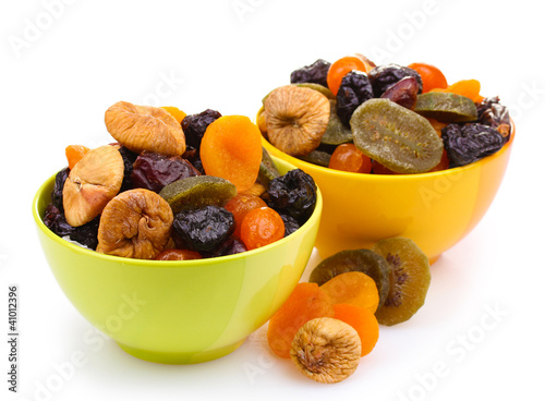 Dried fruits in bright bowls isolated on white