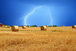 lightning over bales of hay in the field