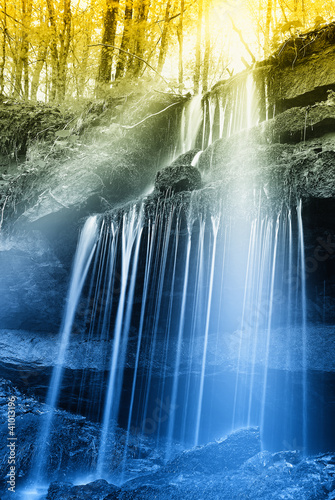 sunbeam over the waterfall in the forest - 41013196