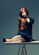 pretty sensual redhead in a black dress sitting on a table