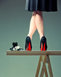 woman legs in shoes with red soles and the camera on a table
