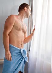 man wrapped towel in bathroom