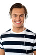 Smiling young man listening to music through headphones