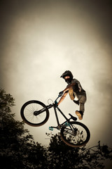 Young man flying on his bike: Dirt jump