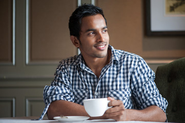 Attractive Indian Male thinking with a drink