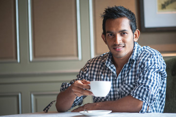 Attractive Indian Male having a drink smiling