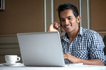 Attractive Indian Male calling and laptop
