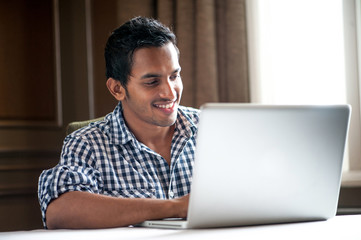 Attractive Indian Male using the laptop