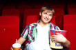 Young man in cinema watching movie