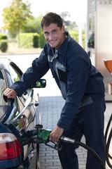 Service station worker refiling car
