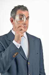 Businessman in a suit looking through a magnifying glass. Isolat
