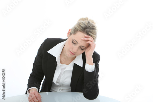Dejected despondent businesswoman sitting at a table